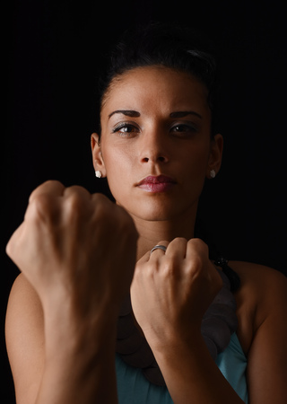 Young woman showing fists in front of black background