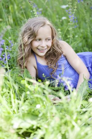 Portrait of smiling girl lying on flower meadow