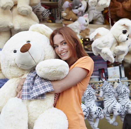 Happy young woman on a funfair hugging large teddy bear LANG_EVOIMAGES