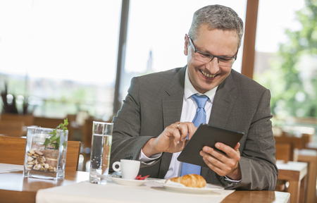 Businessman in restaurant with digital tablet