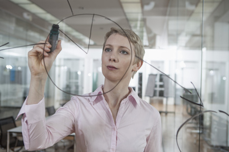 Germany, Munich, Businesswoman in office, drawing chart on glass pane