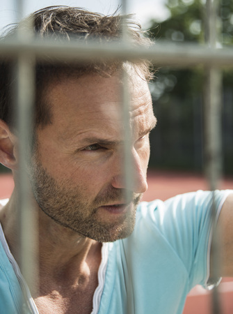 Germany, Mannheim, Man on sports field looking through fence