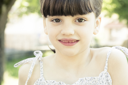 Portrait of smiling little girl with tooth gap, partial view LANG_EVOIMAGES