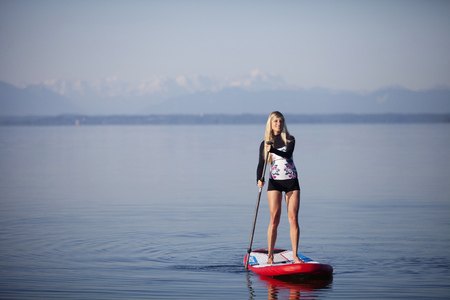Germany, Bavaria, young woman standing on stand up paddle board at Lake Starnberg LANG_EVOIMAGES