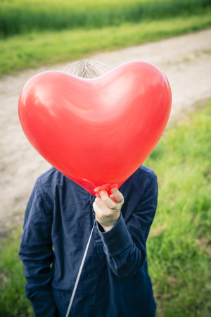 Little boy hiding his face behind a red heart-shaped balloon LANG_EVOIMAGES