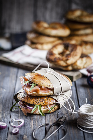 Two garnished home-baked bagels wrapped in paper, string and scissors on wood