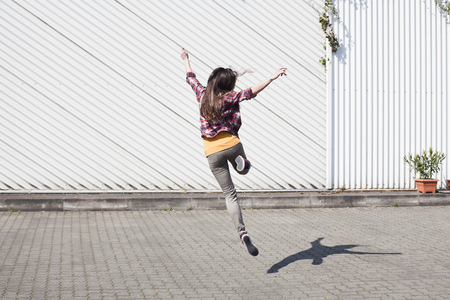 Exuberant young woman jumping outdoors LANG_EVOIMAGES