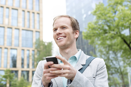 Young man with cell phone outdoors