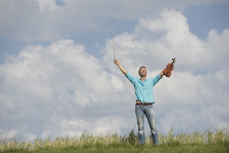 Germany, Bavaria, Starnberg Region, Man playing violin in nature