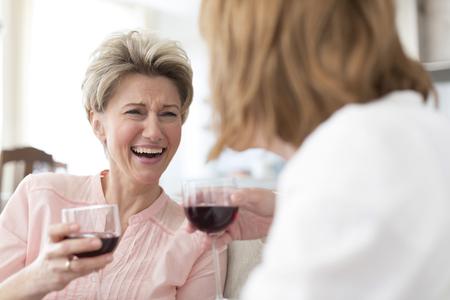 Dos mujeres maduras bebiendo vino tinto en casa