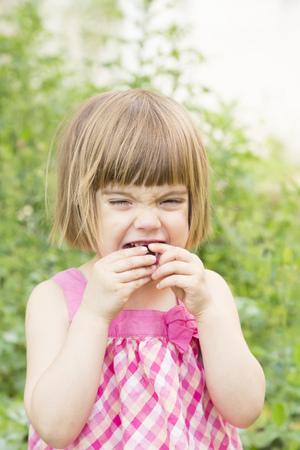 Portrait of little girl eating cherry