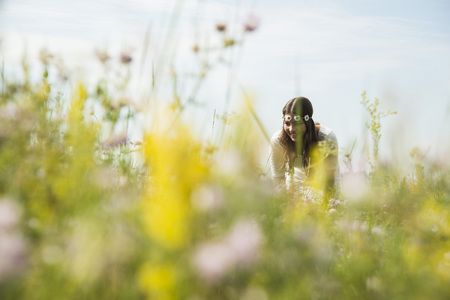 Portrait of smiling young woman standing on flower meadow LANG_EVOIMAGES