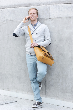 Young man with cell phone leaning against wall