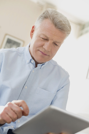 Portrait of man using tablet computer at home