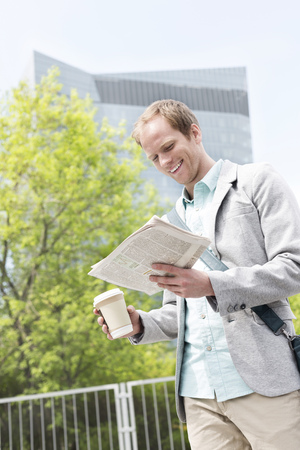 Young man reading newspaper outdoors