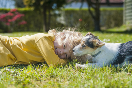 Boy playing with Jack Russel Terrier puppy in garden LANG_EVOIMAGES