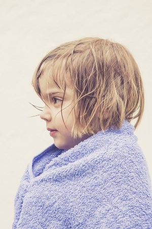 Profile of little girl with wet hair wrapped in a towel