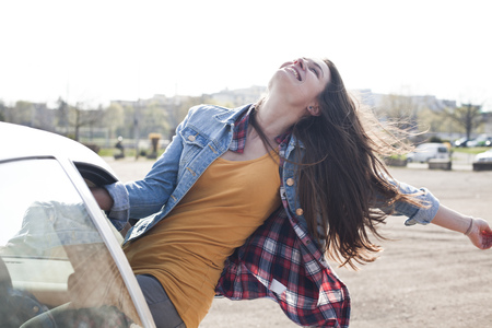 Exuberant young woman leaning out of car window LANG_EVOIMAGES