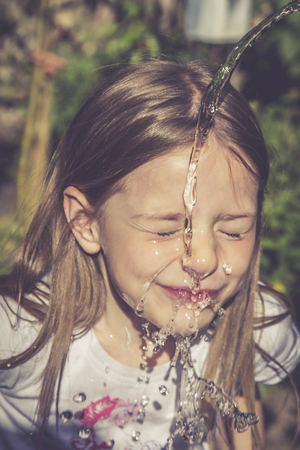 Little girl refreshing her face with a jet of water LANG_EVOIMAGES