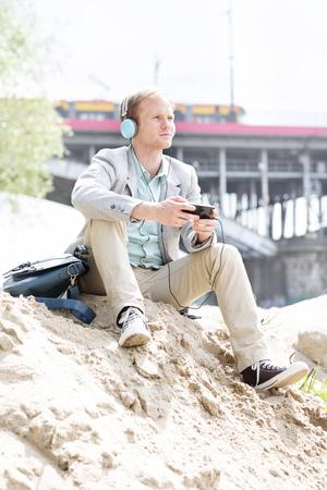 Poland, Warsaw, young man at riverside wearing headphones