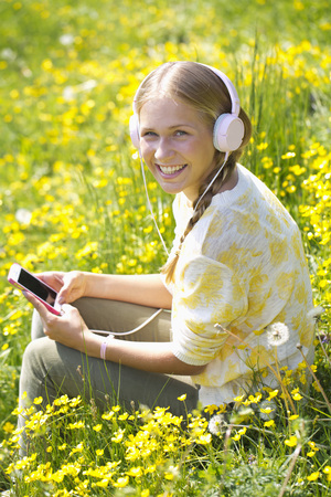 Portrait of smiling teenage girl with headphones hearing music on a flower meadow