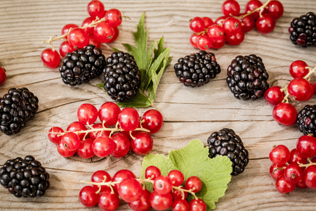 Red currants, blackberries and leaves on wooden table, elevated view LANG_EVOIMAGES