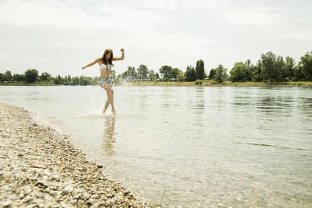 Young woman running at waterside of Rhine river LANG_EVOIMAGES