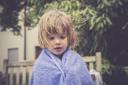 Daydreaming little girl wrapped in a towel