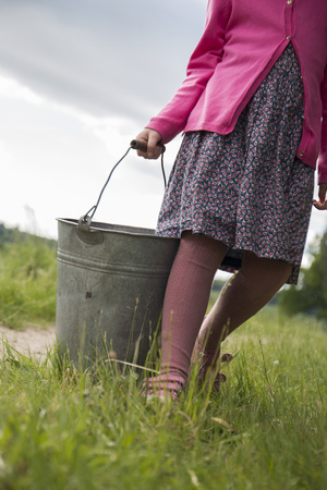 Germany, Schleswig-Holstein, little girl carrying a zinc bucket on a meadow LANG_EVOIMAGES