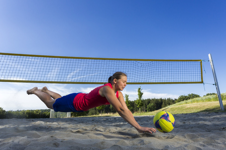Germany, Young woman playing beach volleyball LANG_EVOIMAGES