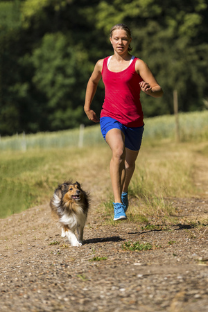 Young woman jogging with dog on field path LANG_EVOIMAGES