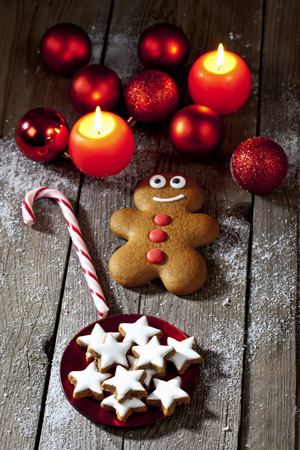 Gingerbread Man, Sugar Cane, Plate Of Cinnamon Stars, Christmas Baubles And Lighted Candles On Grey Wood LANG_EVOIMAGES