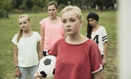 Portrait Of Serious Looking Teenage Girl With Soccer Ball In Front Of Three Other Girls LANG_EVOIMAGES