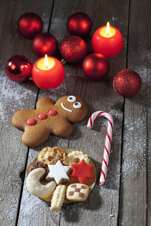 Gingerbread Man, Sugar Cane, Plate Of Christmas Cookies, Christmas Baubles And Lighted Candles On Grey Wood
