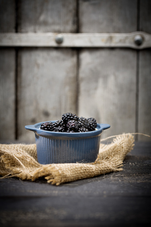 Bowl Of Blackberries, Rubus Sectio Rubus, On Jute And Dark Wood In Front Of Wooden Wall