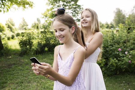 Girl Using Her Smartphone While Her Sister Brushing Her Hair