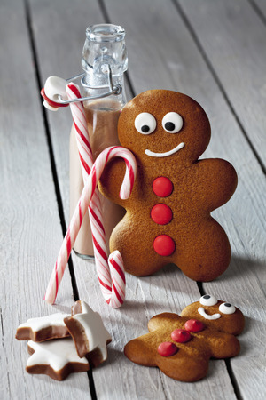 Two Gingerbread Men, Bottle Of Cocoa, Sugar Canes And Cinnamon Stars On Grey Wood LANG_EVOIMAGES