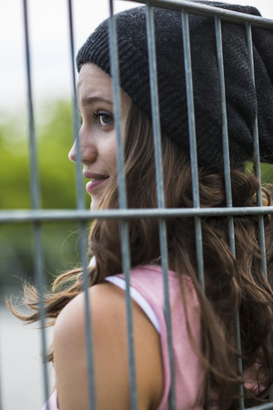 Profile Of Smiling Teenage Girl Behind A Fence Wearing Wool Cap