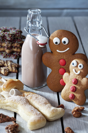 Two Gingerbread Men, Bottle Of Cocoa, Stutenkerl And Christmas Cookies On Grey Wood LANG_EVOIMAGES