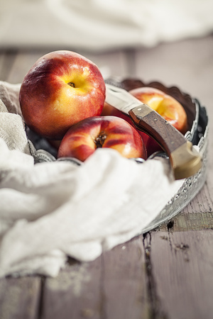 Bowl Of Nectarines And A Knife On Cloth And Wood
