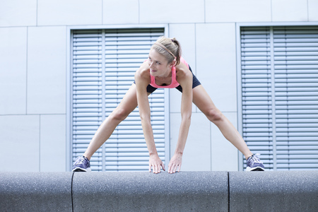 Young Woman Doing Stretching Exercise In Front Of Facade Of An Office Building