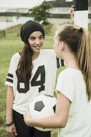 Two Teenage Girls Communicating On A Football Ground