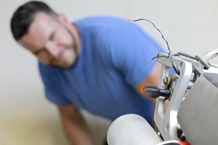 Young Man Examining Enduro Motorcycle