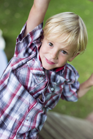 Portrait Of Smiling Little Boy Climbing On Playground Equipment LANG_EVOIMAGES