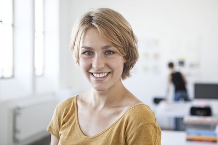 Portrait Of Smiling Young Woman In A Creative Office