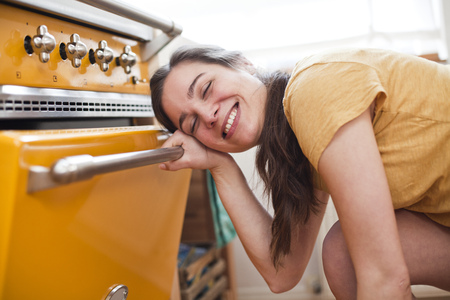 Portrait Of Smiling Young Woman In Front Of Her Oven