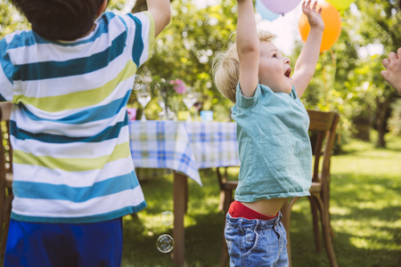 Children Trying To Catch Soap Bubbles In Garden