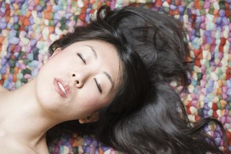 Retrato de mujer asiática con los ojos cerrados en frente de tierra colorida