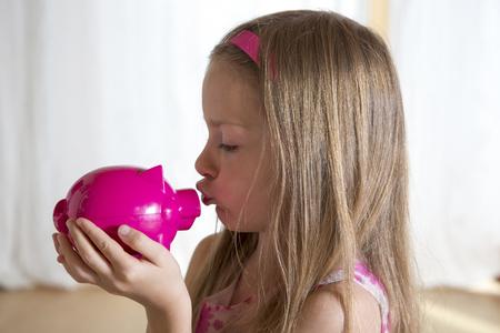 Little Girl Kissing Her Pink Piggy Bank LANG_EVOIMAGES