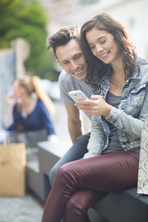 Portrait Of Young Couple Using Smartphone